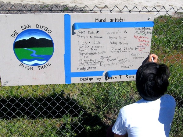 Mural artists sign their names on sign beside the San Diego River Trail.