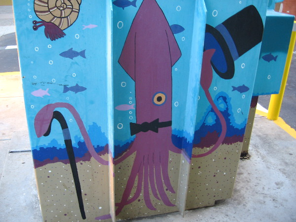 Squid with top hat and cane entertains passersby on a Hillcrest utility box.