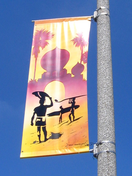 Surfers carry their boards on the beach at Swami's Reef point break.
