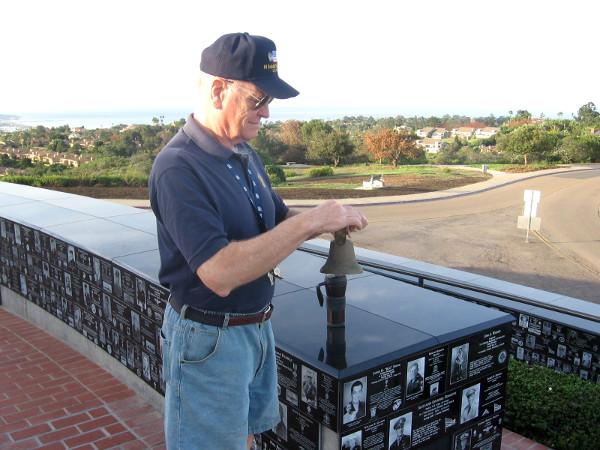 The volunteer at the memorial dutifully rings eight bells.