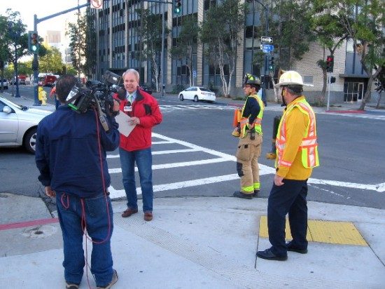 Television reporter and firemen spread the word about today's Fill the Boot campaign throughout San Diego.