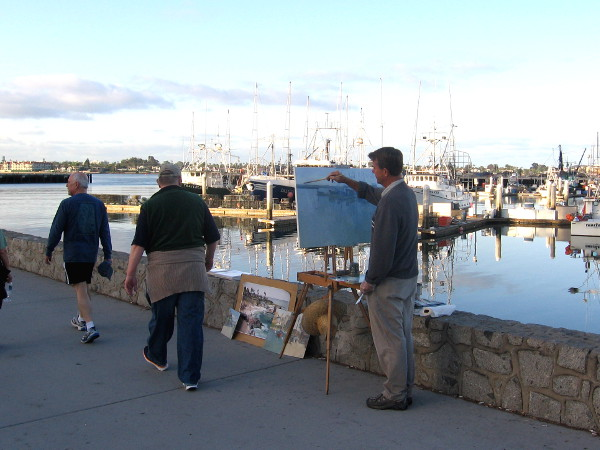 An artist works next to Tuna Harbor as many people stroll past.