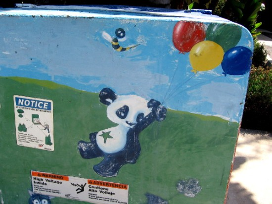 Panda with star on belly is lifted by colorful balloons, and floats away into the blue sky.
