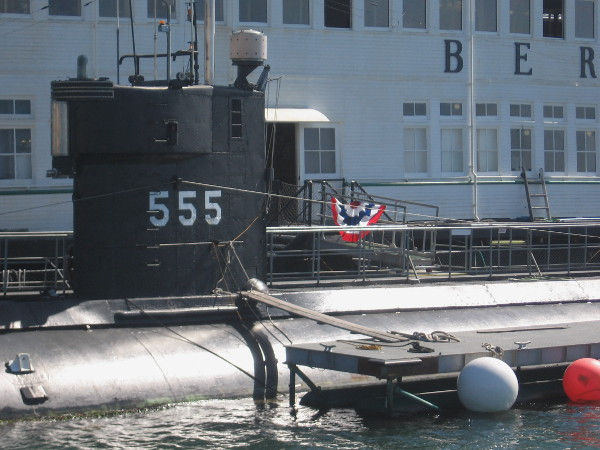 The black sail of submarine USS Dolphin (AGSS-555). The retired research sub is docked next to steam ferry Berkeley of the Maritime Museum of San Diego.