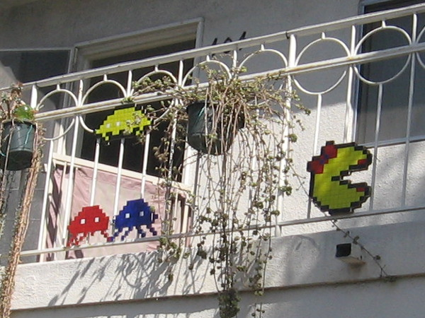 Ms. Pacman, Space Invaders and other video game legends hang out on a porch railing.