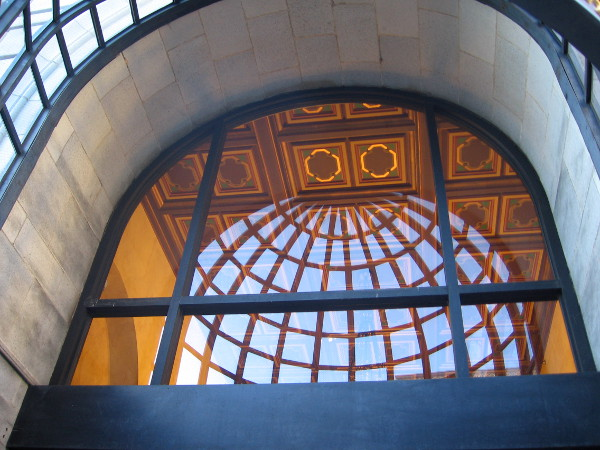 Looking up through the elegant building entrance at the lobby's ceiling.