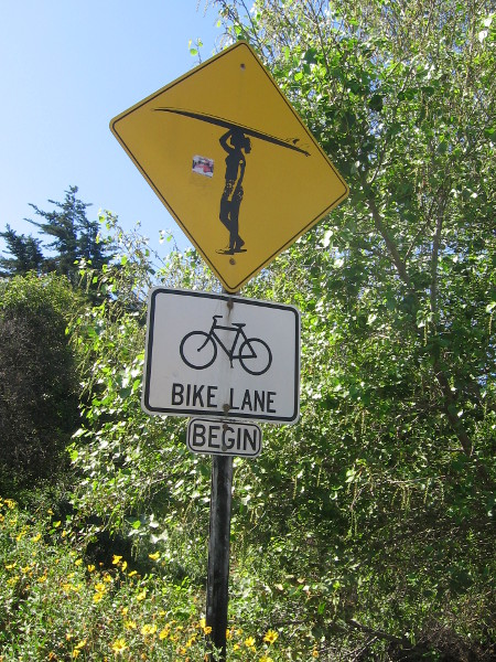 Surfer crossing sign on Pacific Coast Highway near trail to Moonlight Beach.