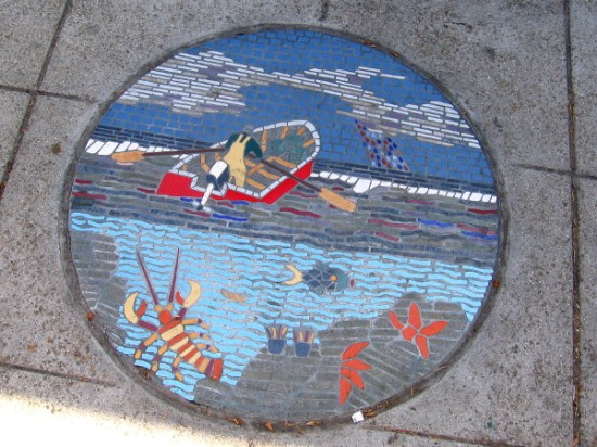 Tile mosaic on Pacific Coast Highway shows fisherman rowing out over the ocean.
