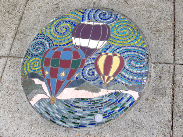 Colored tiles and glass form hot air balloons soaring through a swirling sky.