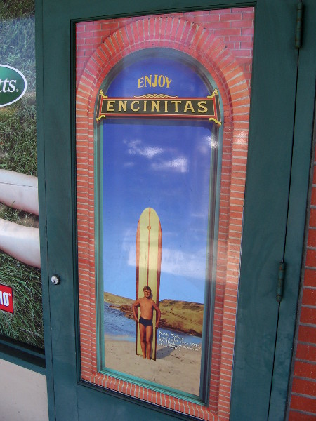 Classic image on building shows surfer and his longboard.