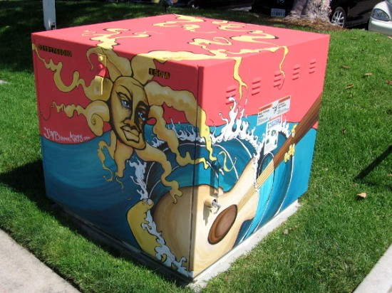 Electrical transformer box decorated with sun, surf and guitar.