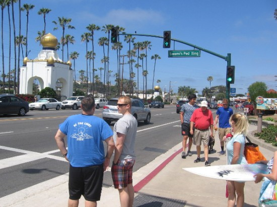 People wait at Swami's pedestrian crossing, with exotic golden domes of the Self-Realization Fellowship across PCH in the background.