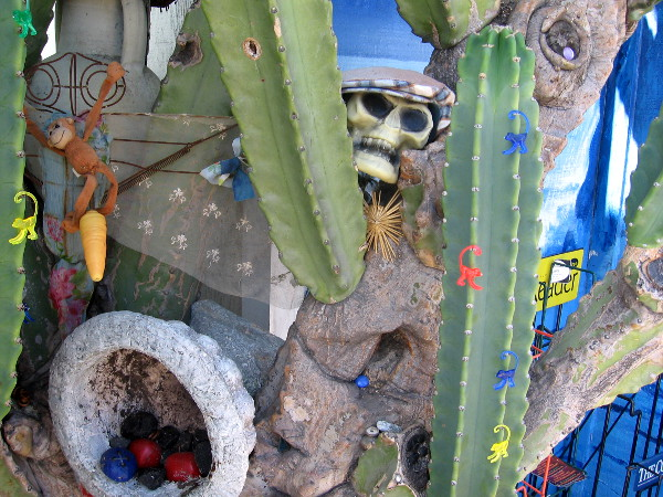 Funky art along sidewalk is hung about a cactus.