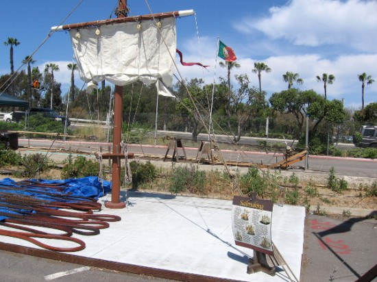View of a small sail suspended from a yard, with Harbor Drive in background beyond the build site.