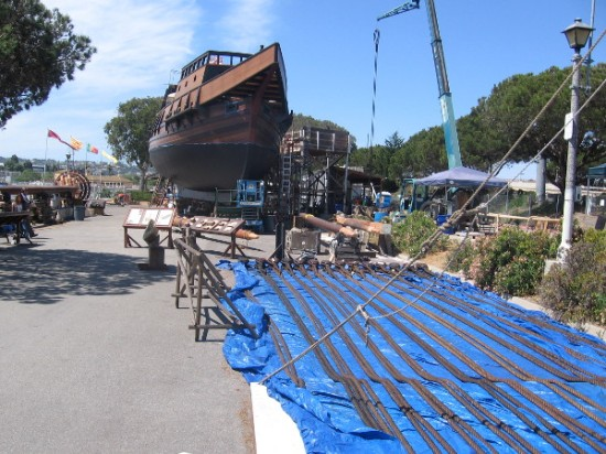 Suspended from a crane is a shroud (rigging that helps hold a mast) that's being tarred. The bow of the galleon comes to a sharp point at its beak.