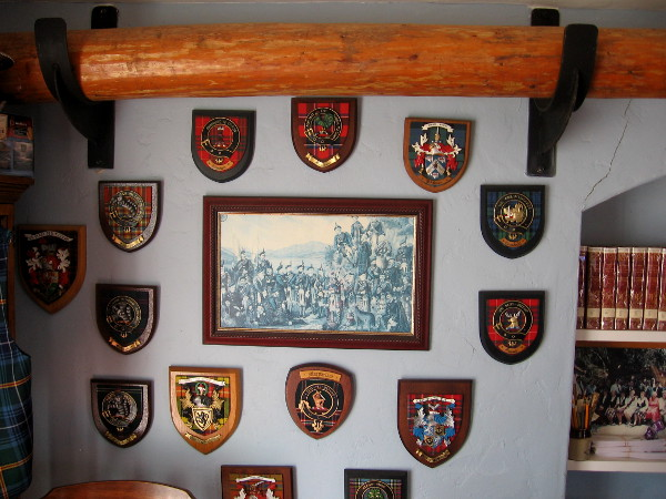 The crests of many diverse clans hang on one wall.