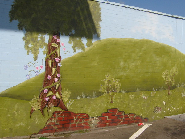 Harsh angular shadow eclipses pastoral mural painted on a parking lot wall.