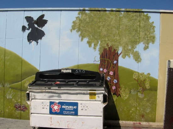 Magical fairy, flowers and tree behind dumpster. A touch of charming creativity in the city.