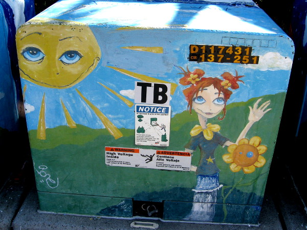 Flowers in hair, on shoulders. A golden star joins the sun and sunflower in symbolic street art.