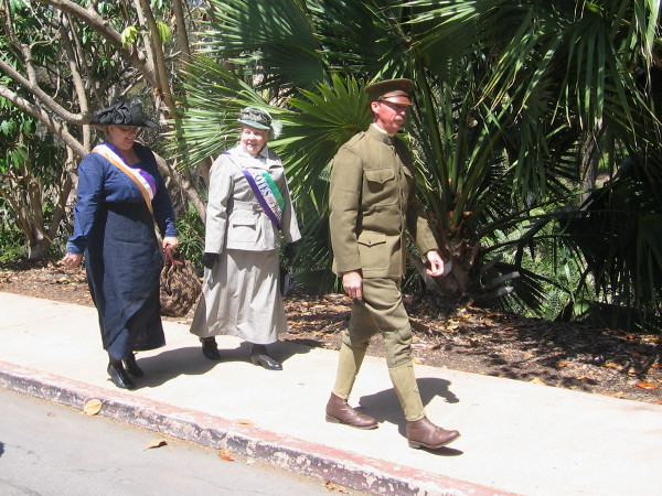 Two suffragettes with Votes For Women sashes follow a guy dressed in World War I era military uniform.