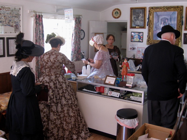 People in period costumes enjoy some treats inside the small cottage.