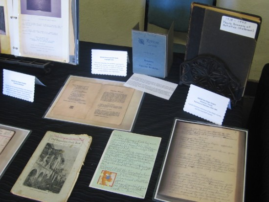 Table includes an Exposition Cook Book, letters, activity books, and other DAR documents.