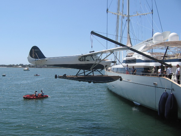 The super-yacht's crane lifts the small seaplane from San Diego Bay into the air!