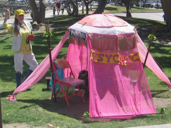This smiling psychic has a bright pink tent!