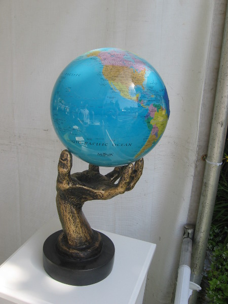 Solar-powered rotating globe held in a human hand.