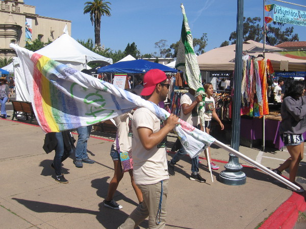 Some guys carry flags in preparation for a small Earth Day parade through Balboa Park.