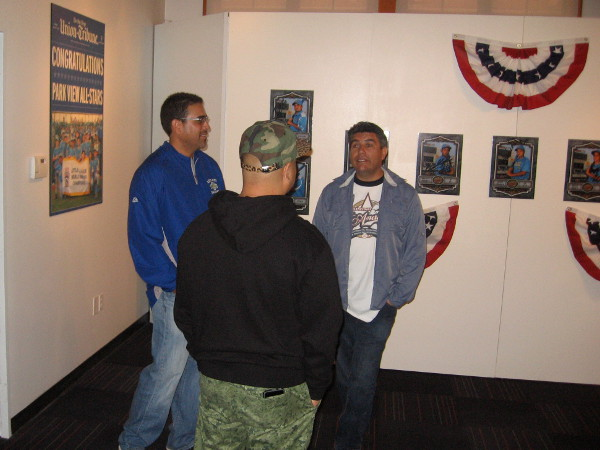 Park View Little League 2009 coach Ric Ramirez talks with visitors at cool New Americans Museum exhibit.