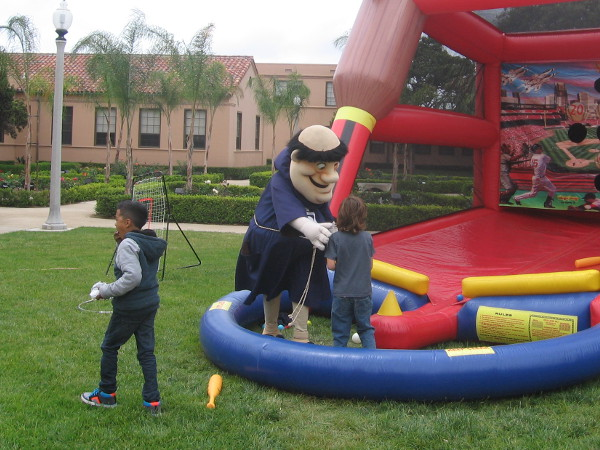 Padres baseball mascot the Swinging Friar plays with kids at the batting inflatable outside during the museum event.