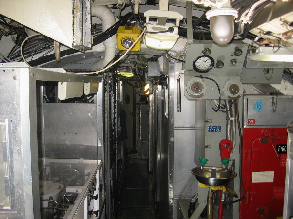 Starting along the very narrow main hallway. This unusual sub contains no compartments. To the left one can see a reverse osmosis water filtration system.