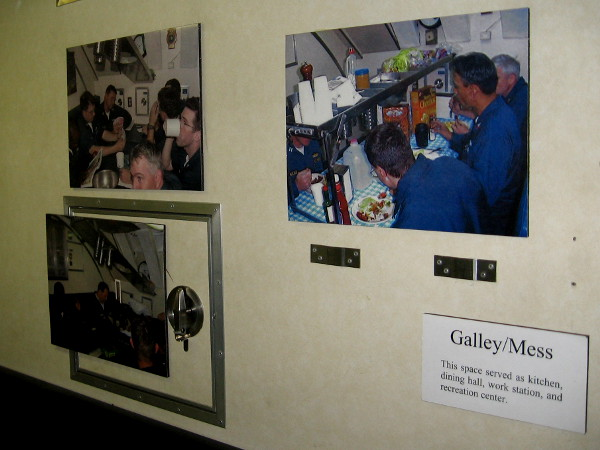 Photos on wall of tiny mess area show what life was like aboard Dolphin.