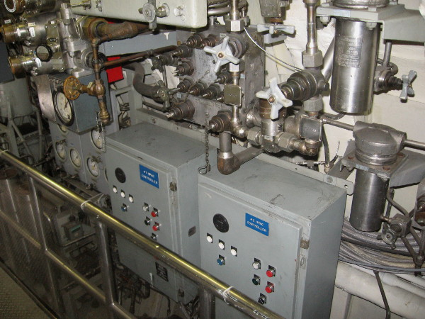 High-Pressure Air Compressor Controllers among a jumble of pipes and valves.