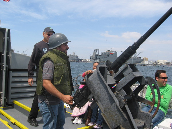 Guy enjoying the tour dons helmet and mans the Swift Boat's old 50 caliber machine gun, which is mounted over a 81mm mortar.