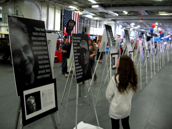 Visitor to USS Midway Museum on Memorial Day weekend absorbs Portraits of Resilience exhibit, created by students of High Tech High Charter School.