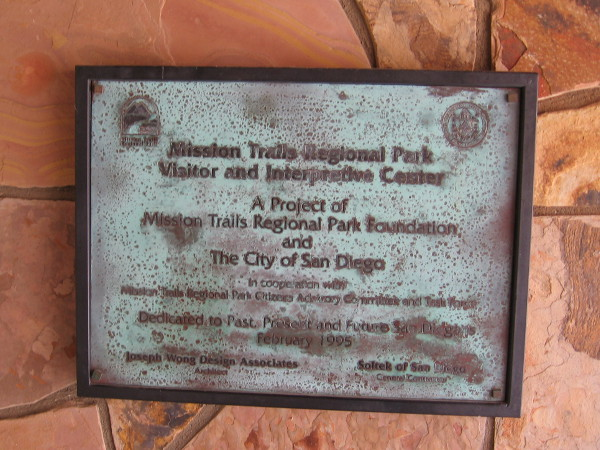 Plaque by door dedicates the large open space park to past, present and future San Diegans.