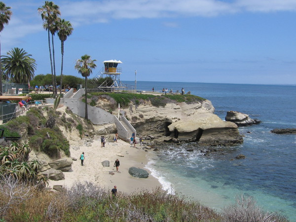 A lifeguard tower rises above La Jolla Cove Beach. To the right of the tower is Point La Jolla.