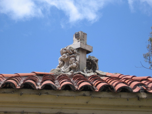 A close look at the plaster artwork at the top of one guardhouse's tile roof. The hundred year old material has crumbled.