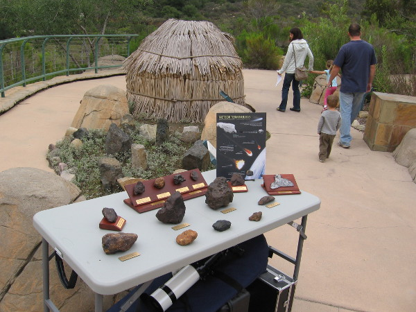 Cool table full of meteorites next to traditional Kumeyaay house made of willow branches.