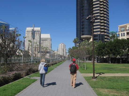 Two people walk side-by-side down the Martin Luther King Jr. Promenade in downtown San Diego.
