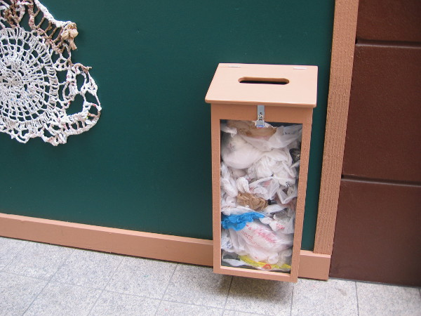A box by the fantastic plarn sculpture invites passersby to recycle their plastic shopping bags.