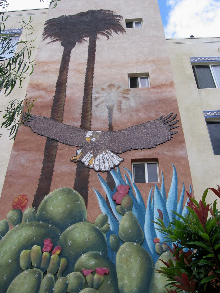 Cool mural on residential building features an eagle, cacti, palm trees.