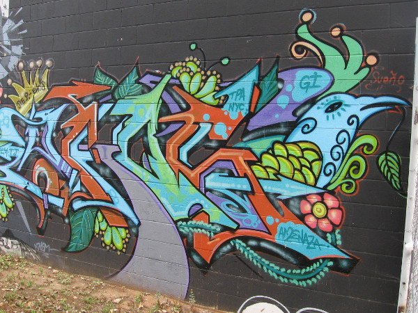 Portion of colorful graffiti in a weedy space between buildings.