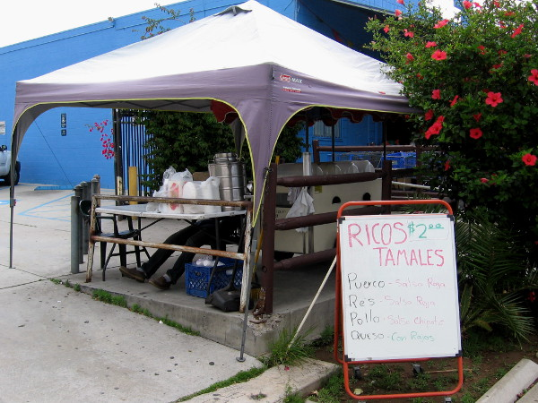 Local vendor is selling tamales under a canopy by the sidewalk.