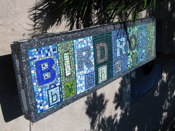 Bench on La Jolla Boulevard sidewalk spells out Bird Rock with colorful tiles.