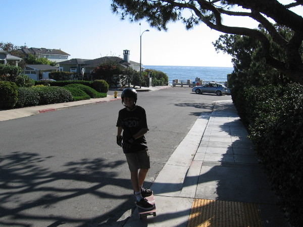 Kid skateboards down hilly Bird Rock Avenue toward the small lookout point.