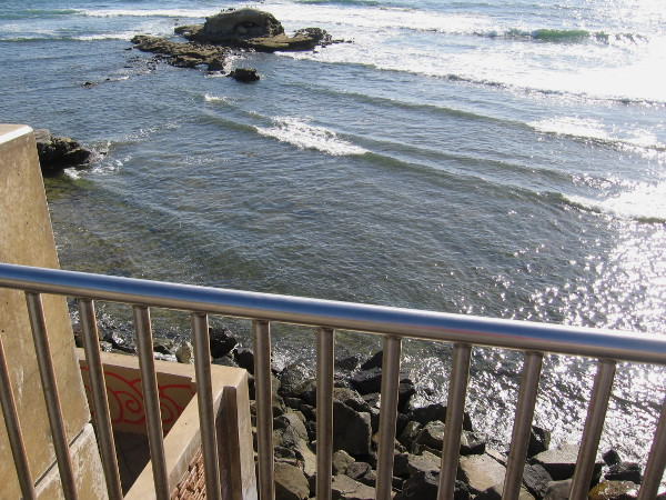 Looking down over the view point rail at rugged rocks at the edge of the shining Pacific Ocean.