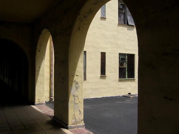 Photo of shuttered windows taken through dark, weathered archway.